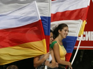Local residents celebrate while holding South Ossetian and Russian flags in the main South Ossetian city of Tskhinvali