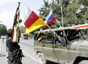 South Ossetian servicemen fire their weapons and wave South Ossetian and Russian flags as they celebrate Russia's recognition of their state as an independent state in Tskhinvali
